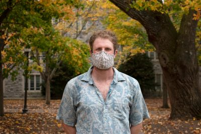 Virginia Tech College of Science Ph.D. student Ben Kligman  poses wearing a mask near Williams Hall on the Virginia Tech campus. Trees, with orange and yellow leaves, surround him. Photo by Steven Mackay.